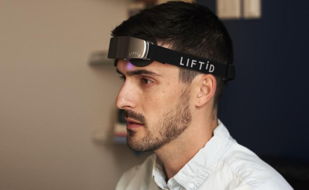 A side view of a man wearing a brain stimulation device headband.