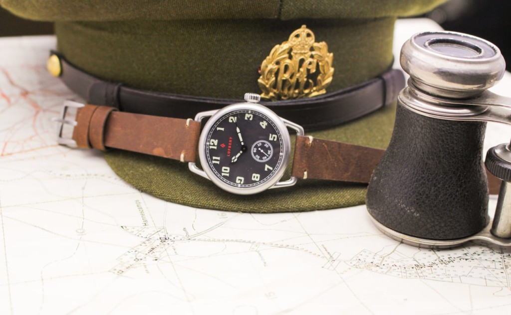 A brown and silver trench watch on a green military cap.