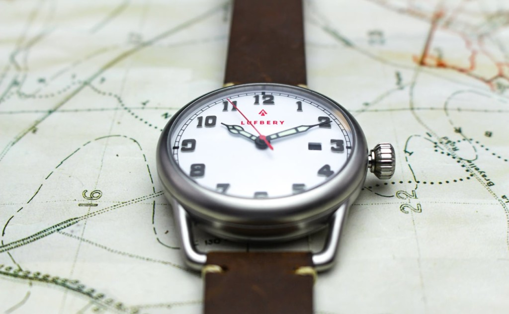 A silver trench watch with a white face and a brown leather band on top of a map.