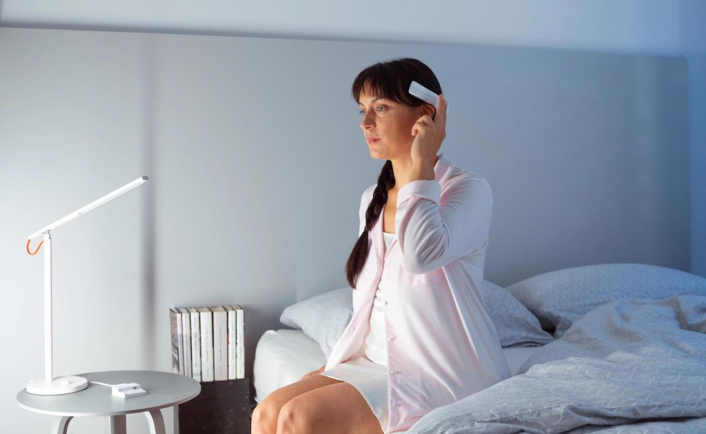 A woman is sitting on the edge of a bed and lifting her fingers to tap on the white stress-reducing headband she is wearing.