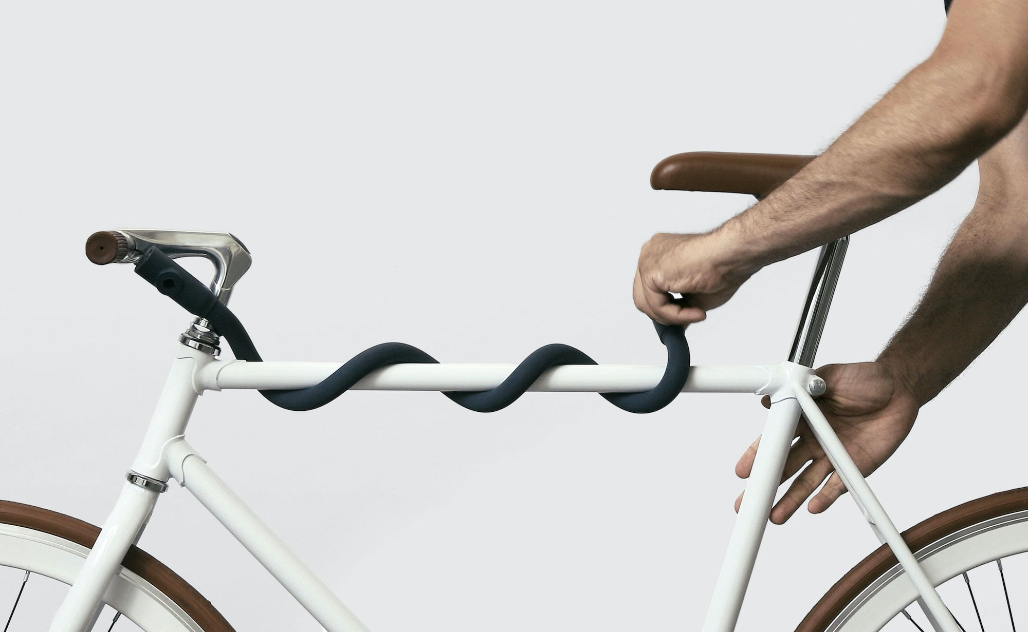 The multi-shape bike lock is wrapped around the center bar of a white bike frame.