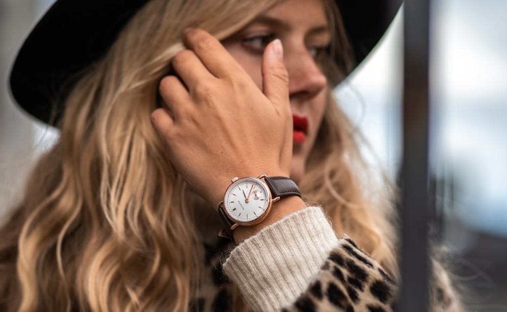 A woman reaching up to brush her hair away from her face, and on her wrist is an elegant watch.
