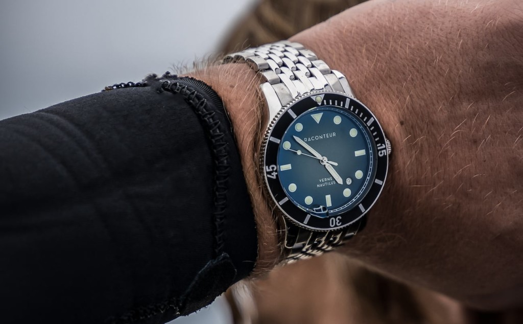 A man's wrist with a watch with a metal band and a blue dial is on his wrist.