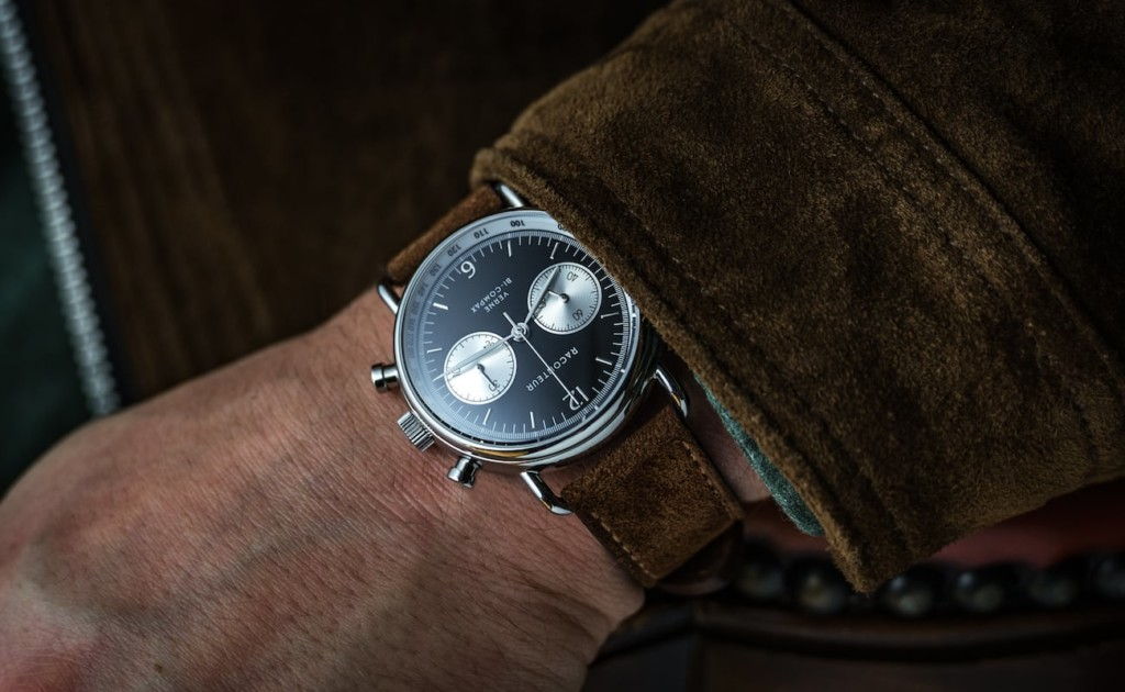 A man's wrist with an elegant watch on it with a reverse panda dial.