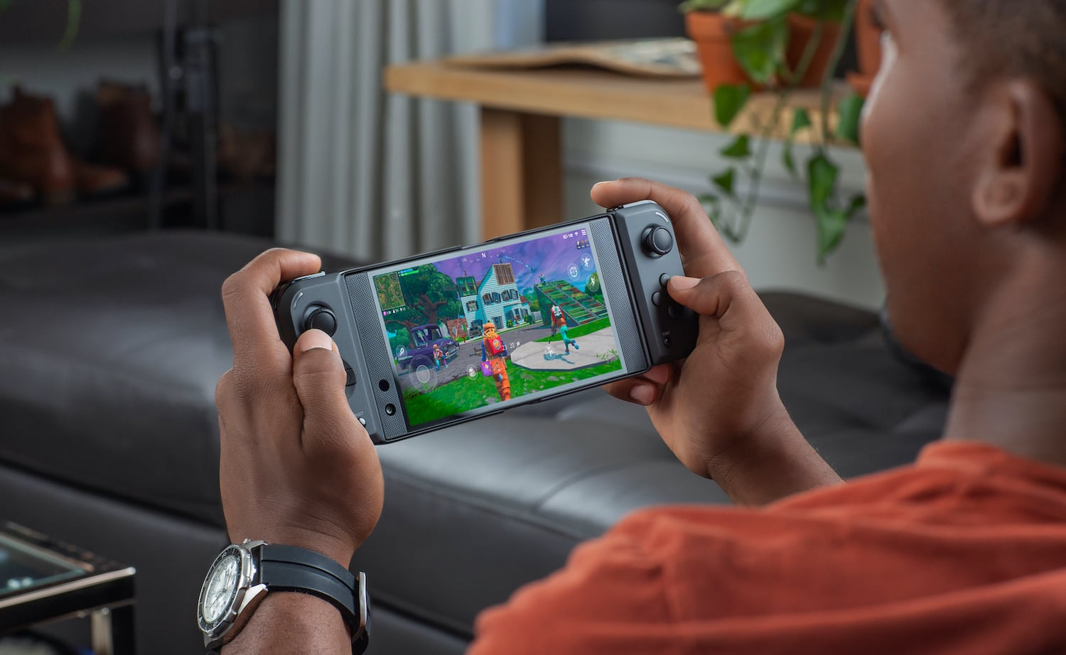 View from behind of a person holding the Android gaming controller and playing a game on it