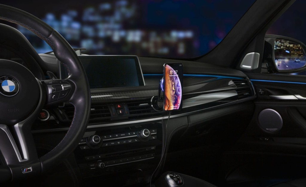 A picture of a black car dashboard with a smartphone attached to a fast-charging car mount.