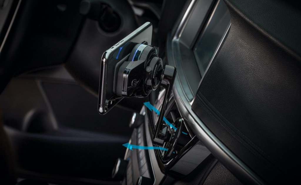 A rear view of a fast-charging car mount attached to an air vent with blue arrows coming from the air vent it indicate air flow.