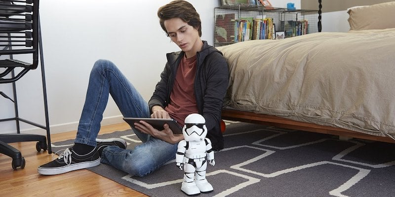 A man sitting on the floor by a bed with a best robots Stormtrooper robot on the floor next to him,