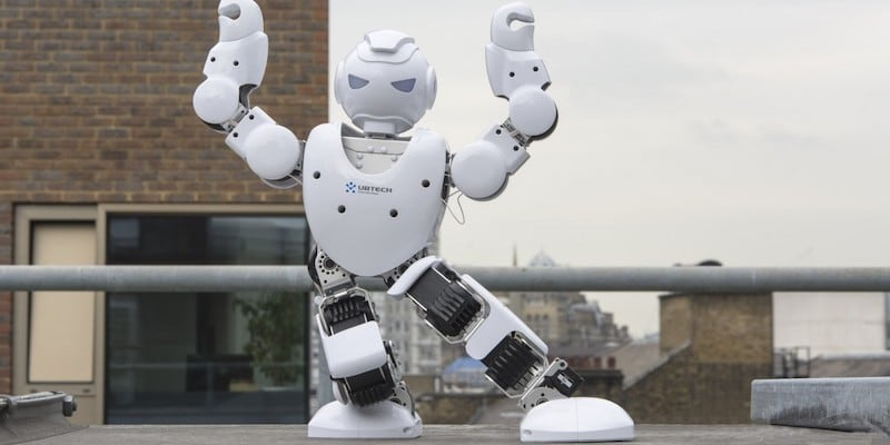 A white best robots humanoid robot with its arms in the air.