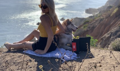 A woman and a dog sitting beside a solar-powered latest tech gadgets charger.