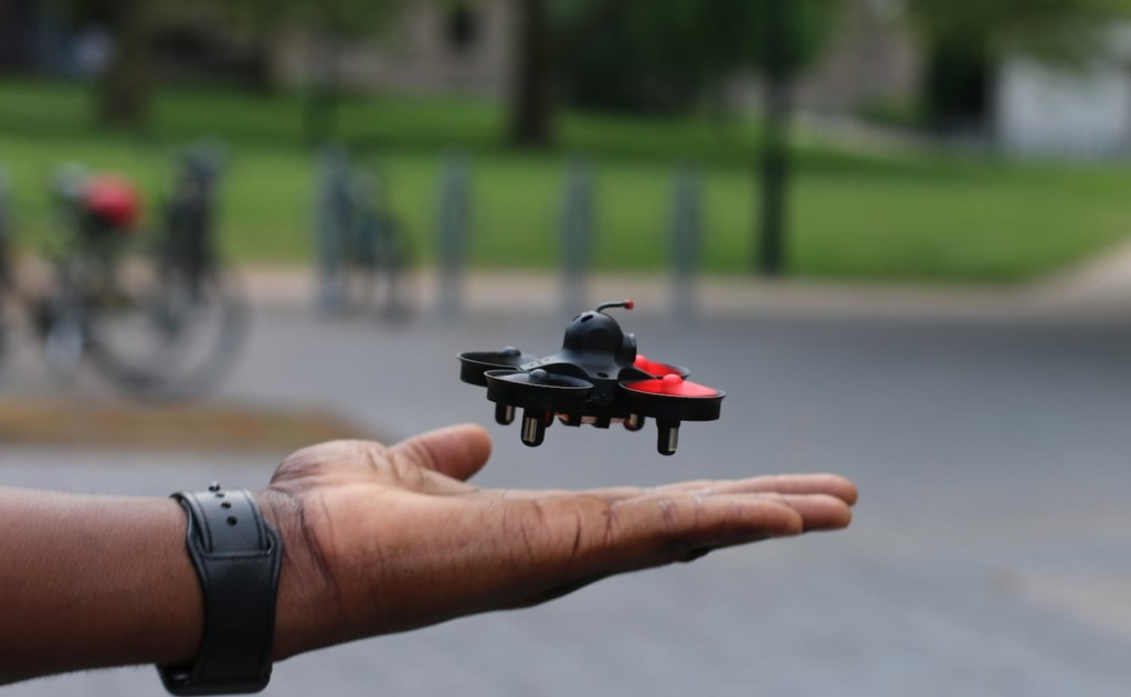 A small latest tech gadgets drone floating about an outstretched hand.