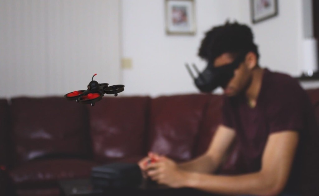 A man in the background in goggles, and a small latest tech gadgets drone in the foreground.