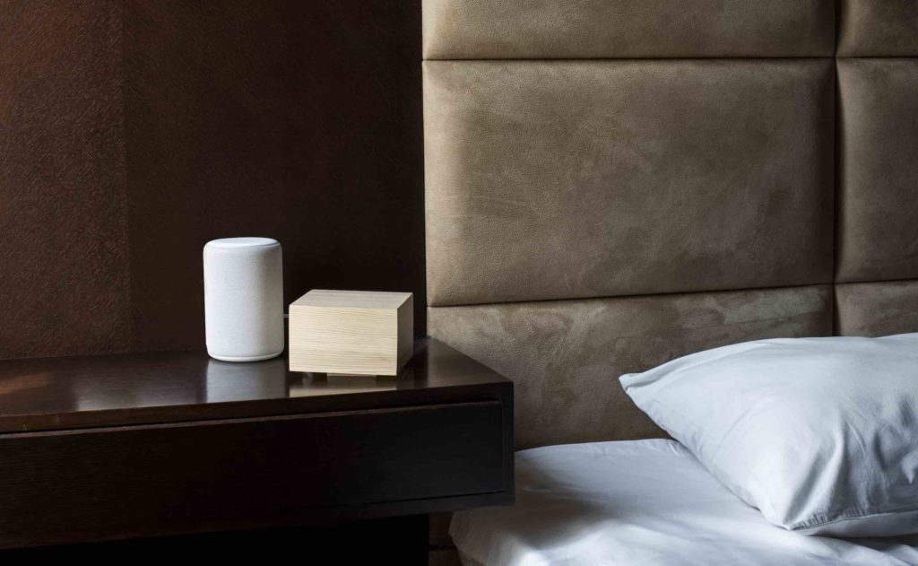 A small tan latest tech gadgets sleep light next to a bed on a nightstand.