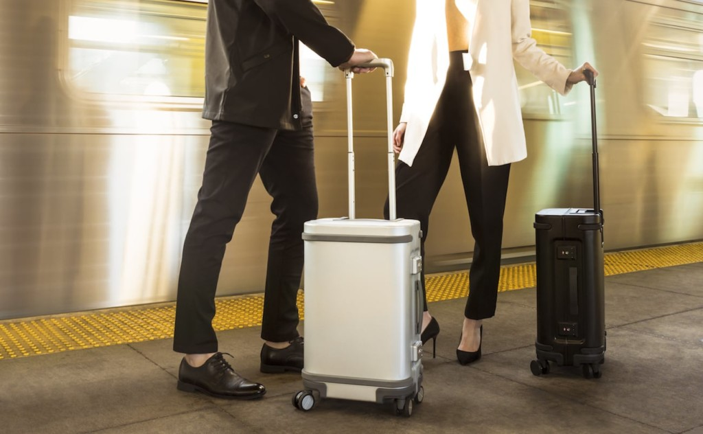 A man and a woman standing with latest tech gadgets suitcases.