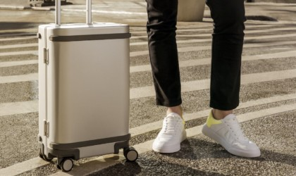 A close up of a latest tech gadgets smart suitcase with a person standing beside it.