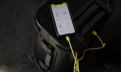 A phone open to the app for a latest tech gadgets smart suitcase; the phone is on top of the smart suitcase.