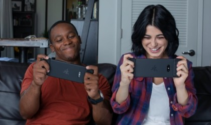 A man and a woman using latest tech gadgets gaming controllers on their phones and smiling.