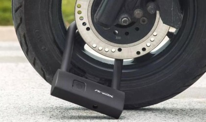 A black latest tech gadgets smart lock attached to a tire.