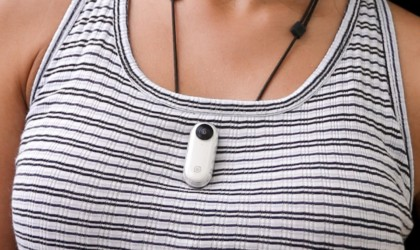 A woman with a small white latest tech gadgets video camera attached to her shirt.