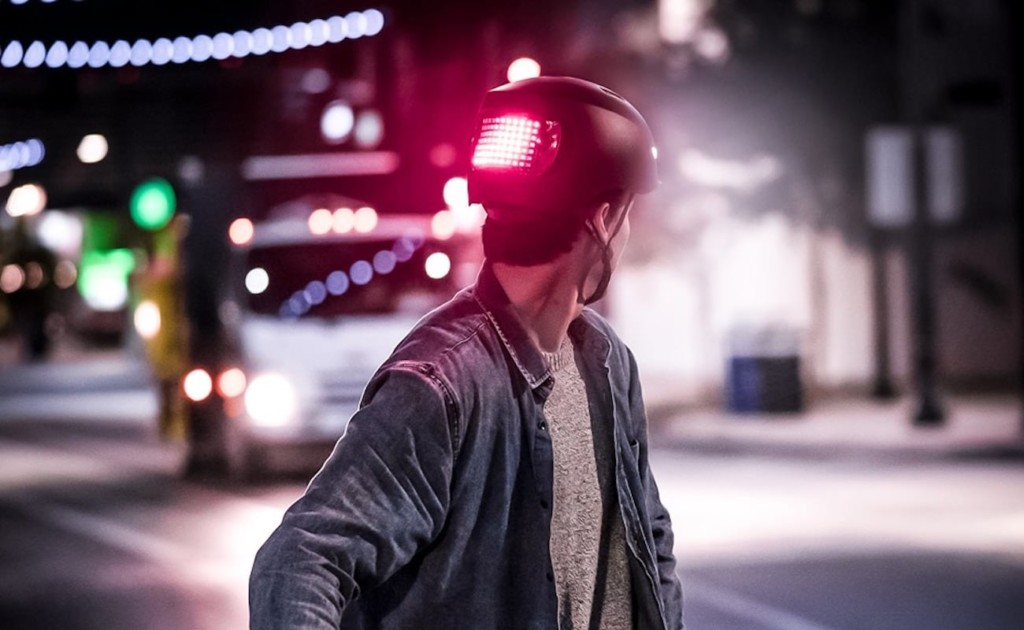 A man with his head turned in a latest tech gadgets bike helmet with a red light on it.