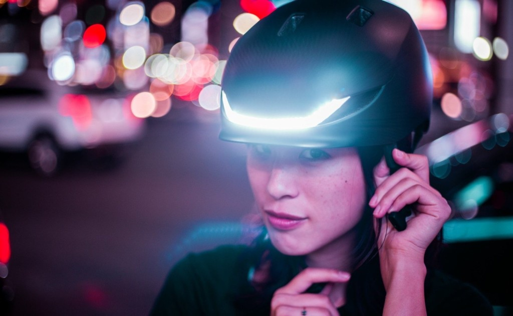 A woman wearing a latest tech gadgets bike helmet with a white light on the front of it.