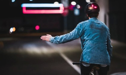 The back of a man riding a bike with a latest tech gadgets lighted bike helmet on and his left arm outstretched.