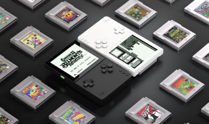 One black and one white latest tech gadgets handheld video game system on a black table, surrounded by video game cartridges.