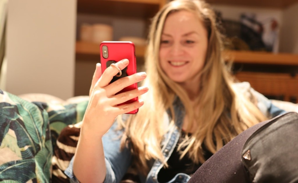 A woman is smiling and holding up a red smartphone, her finger through a ring hands-free phone accessory on the back of the phone.