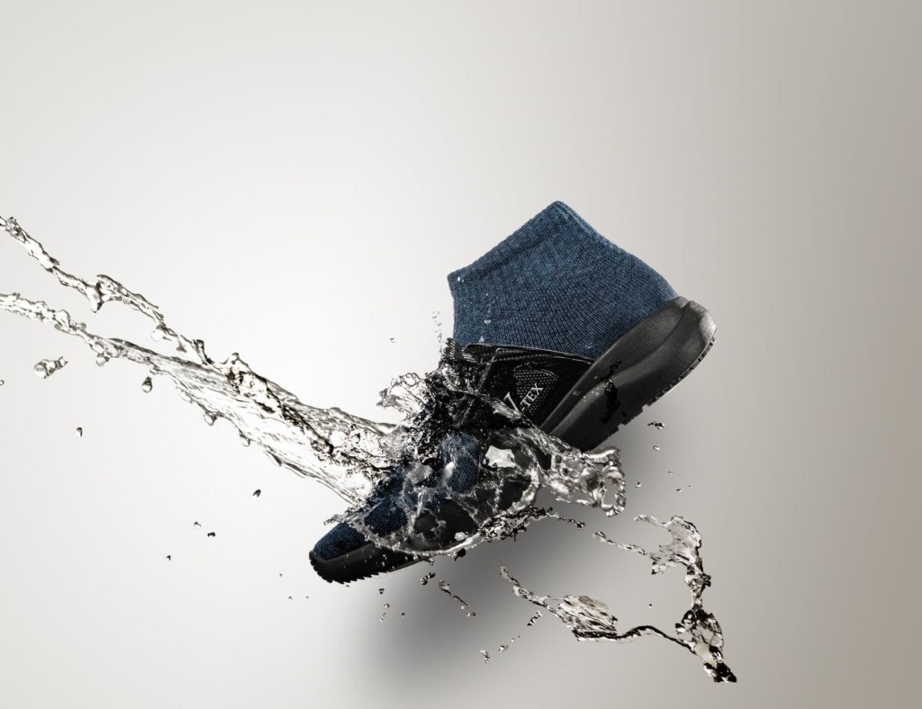 A black and blue high top waterproof shoes with a stream of water coming down on it.