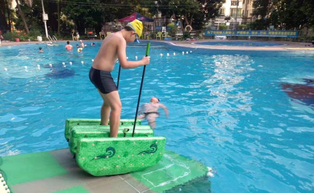 A man with a pair of green beach toys on his feet, standing at the edge of a pool.