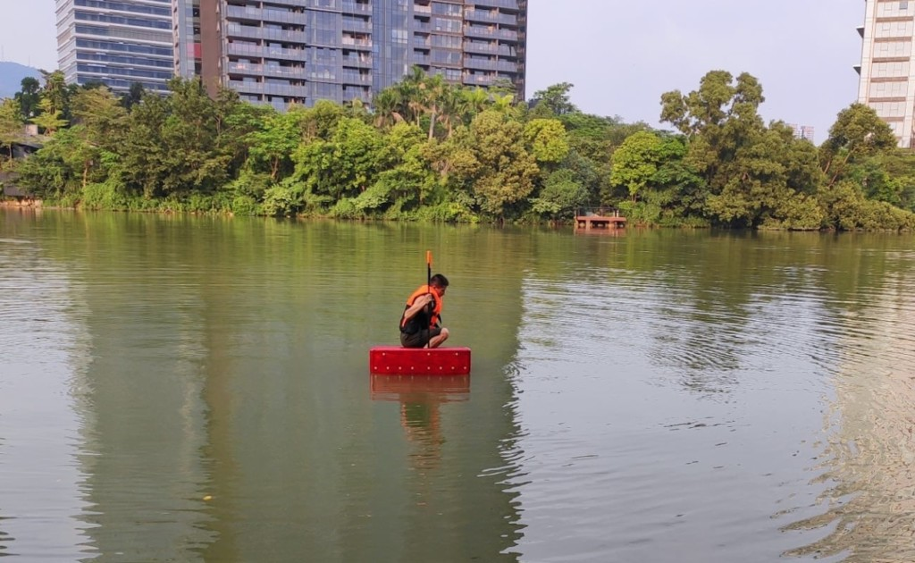 A man is in the river wearing large red Walk on Water shoes, crouching down.