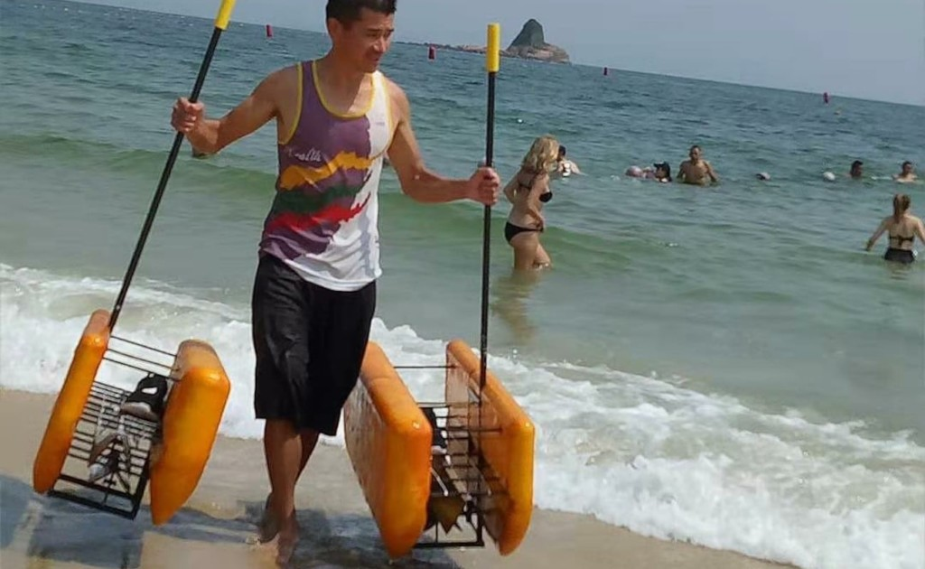 A man carrying two orange Walk on Water devices on the beach.