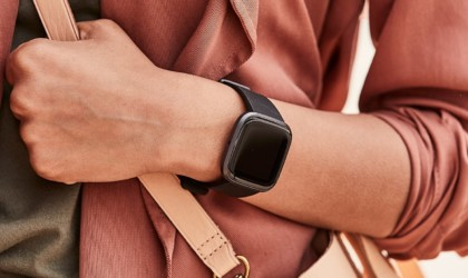 A black health tracking device watch on a woman's wrist.