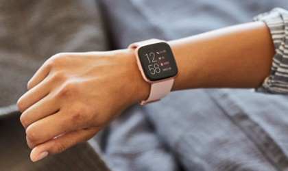 A pink health tracking device watch on a woman's wrist with the time on the display.