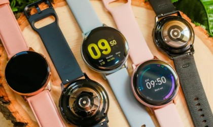 A row of multicolored health tracking device watches with different faces on them.