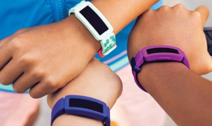 The hands and wrists of three children, each wearing a health tracking device watch.