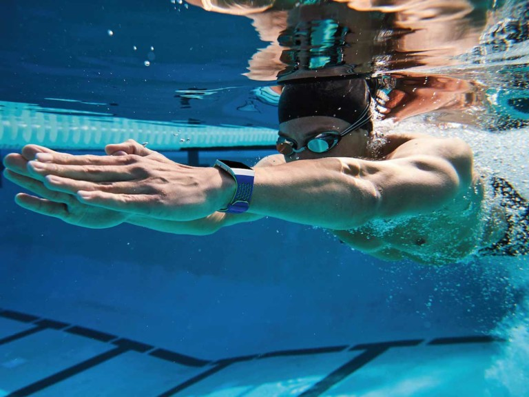 A man swimming in a pool underwater with a health tracking device watch on his wrist.