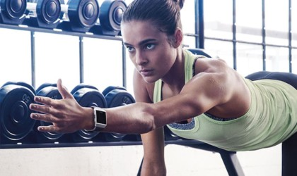 A woman exercising in the gym, and her outstretched arm has a health tracking device watch on it.