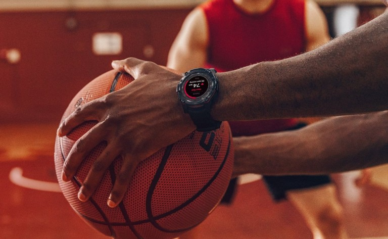 A pair of hands holding a basketball, a health tracking device watch on one wrist.
