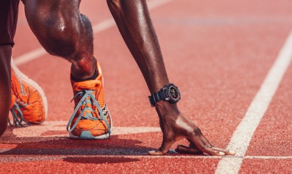 A close up of the arm and leg of a person on a running track, with a health tracking device watch on their wrist.