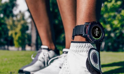 A close up of the lowers legs and sneakers of two people, and one is wearing a health tracking device watch on their ankle.