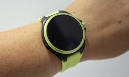 A light green health tracking device watch on a wrist.