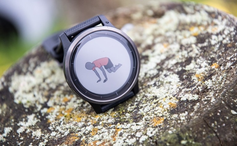 A health tracking device watch on a rock with the image of a person doing yoga on the face of the watch.