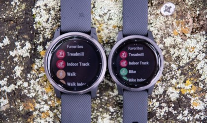 Two black health tracking device watches side by side on a rock
