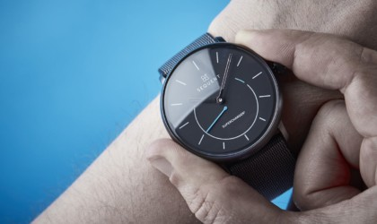 A person wearing a black health tracking device watch on their wrist and holding either side of the watch face.