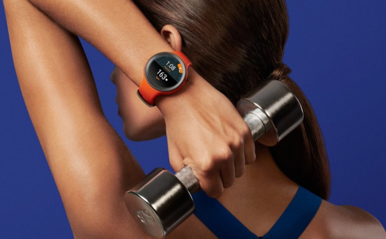 A woman holding a hand weight behind her hand, and she is wearing a red health tracking device watch.