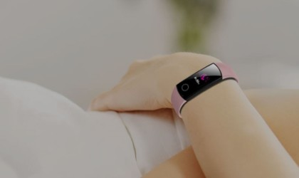 A close up of an arm, and there is a pink watch on the wrist.