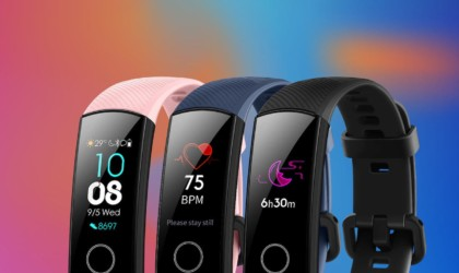 A row of health tracking device watch, and the watches are pink, navy blue, and black.