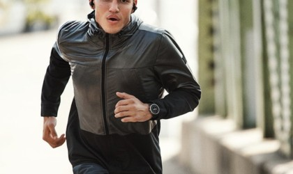 A man in black clothes is running outside on a sidewalk.