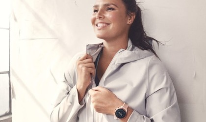 A woman is standing against a wall wearing a pink health tracking device watch, smiling and zipping up her white jacket.